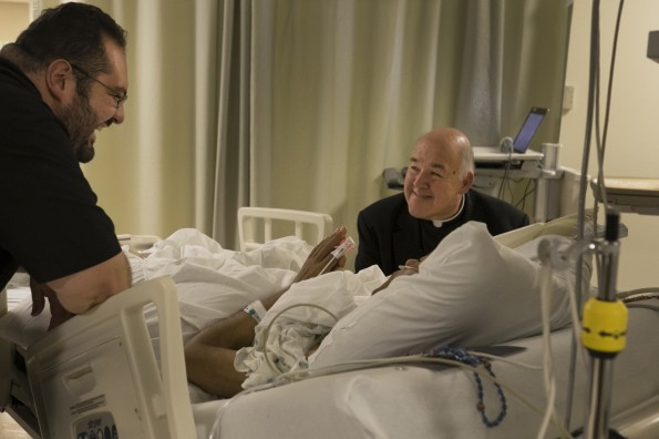 Tennessee bishop and priest talk with gravely ill seminarian in intensive care room at Texas hospital